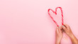 canvas print picture - Candy cane in shape of heart in woman hands on pink