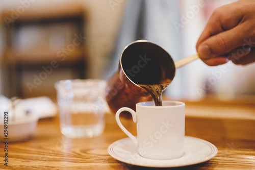 Blurred barista background. Fresh espresso coffee is poured into white ceramic cup made of cezve