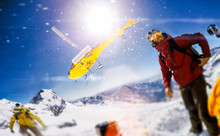Actionsportlers Were Dropped By A Helicopter At The Top Of The Mountains While One Person Is Taking A Smile Selfie With A Wide Angle Camera.  The Sun Is Shining Brightly In The Blue Sky. There Is A Mo