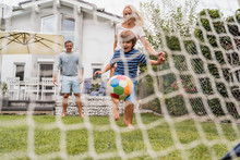 Happy Family Playing Football In Garden