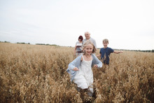 Portrait Of Happy Girl Running In An Oat Field While Brother, Grandmother And Grandfather Following Her