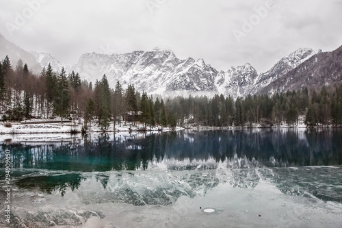 lake with green forest and snowy mountains in the background and skyfall effect Canvas Print
