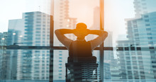 Portrait Of Relaxed Businessman In Modern Office.Business Young Man Relax After Work Of Office Window With Business District View.