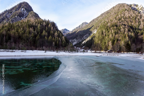 Photo  Beautiful view at sunset of the peaceful lake Fucine Tarvisio, Italy with green forest and snowy mountains in the background