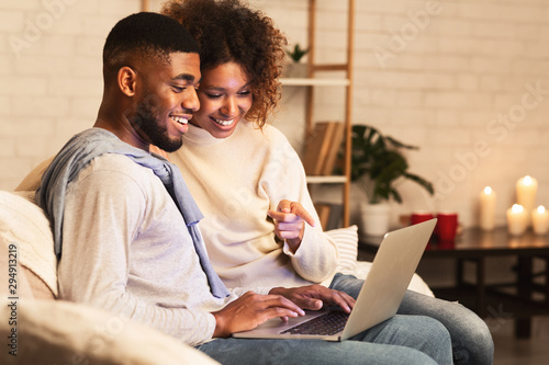 Poster Individuel Loving afro couple choosing film on laptop, resting in cozy room