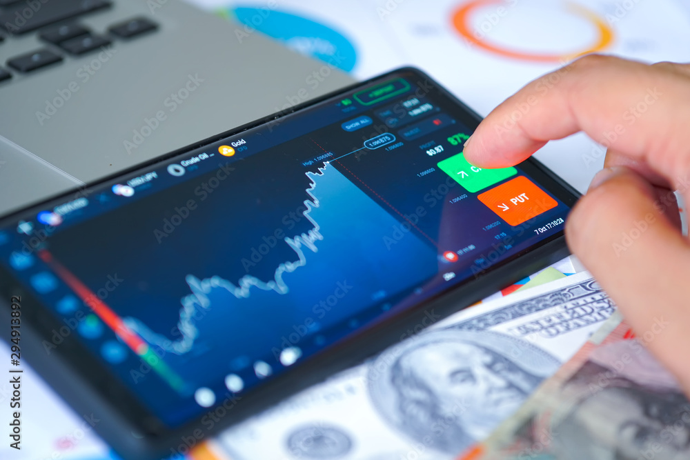 Fototapety, obrazy: Business and Financial Concept. Finger touch the screen for online trading with chart display on smartphone