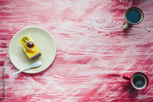 Cake with berries on a ceramic plate standing on a wooden background.