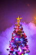 canvas print picture Christmas tree with festive lights, purple background with smoke