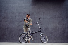 Full Length Of Smiling Handsome Caucasian Fashionable Man Leaning On His Bicycle And Holding Smart Phone And Glasses. In Background Is Gray Wall.