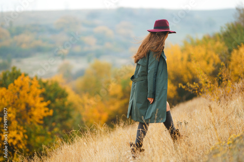 Obraz Beautiful young stylish girl in a coat walks in the autumn in the park. The girl is dressed in a green coat and a red hat. Beautiful evening. Autumn fashion. Lifestyle. High fashion portrait.  - fototapety do salonu