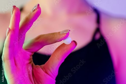 Woman's hand close-up holding drug pill in neon light Fototapete