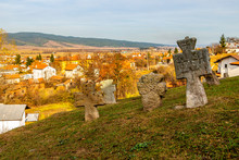Rear View Of Ancient Stone Crosses At The Churchyard Of St. Petka Eastern Orthodox Church In Tsari Mali Grad Fortress, The Village Of Belchin, Bulgaria In The Background