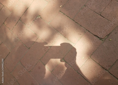 red bricks with shadow of person with camera or phone