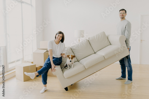 Obraz na plátně  Happy couple move furniture in their new modern home, carry sofa with pet, pose