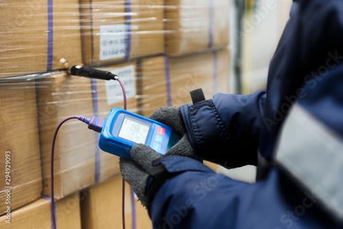 Fotografie, Obraz Hand of worker using thermometer to temperature measurement in the goods boxes w