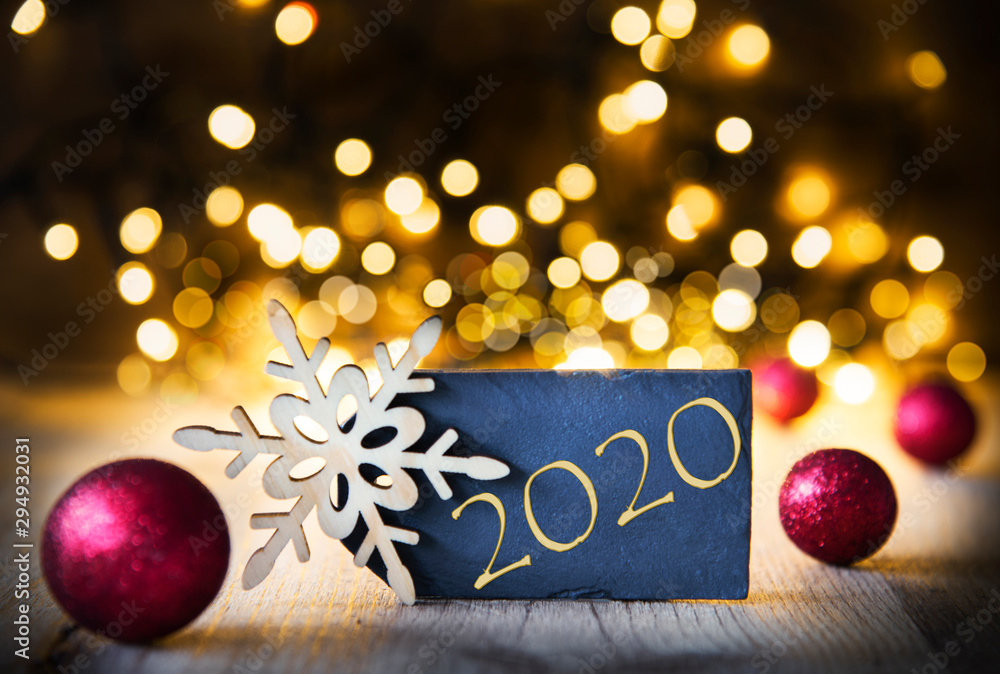 Fototapeta Plate With Golden Text 2020 For Happy New Year Greetings. Bright Glowing Lights In The Background. Christmas Ornament Like Red Balls And Snowflake.