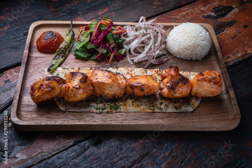 Photo Turkish chicken sis kebab with rice and vegetables isolated on rustic wooden tab