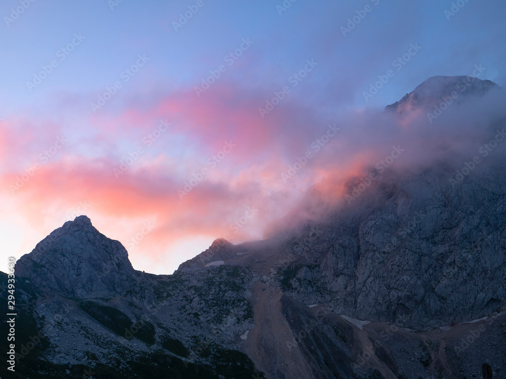 Cinematic shot of clouds rolling over the mountaintop on a tranquil evening.