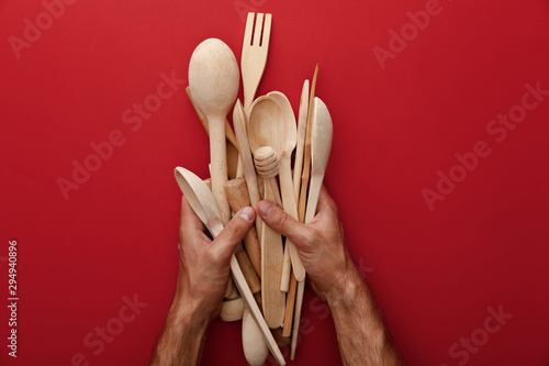 Fotografía cropped view of man holding wooden spoons, fork and kitchenware on red backgroun