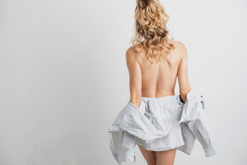 Young blonde woman's bare back, facing away from the camera, removing her shirt.
