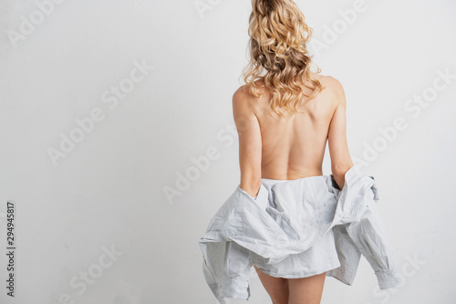 Obraz na plátně Young blonde woman's bare back, facing away from the camera, removing her shirt