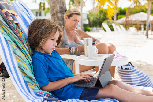 Boy using laptop at beach while mother sitting in background - 294947031