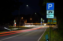 A Square Blue Sign Indicates A Parking Lot For Campers At A Distance Of 2 Kilometers. At Night In Germany In Front Of A Crossing With City Lights.