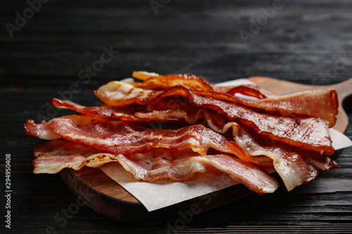 Slices of tasty fried bacon on black wooden table, closeup Wallpaper Mural