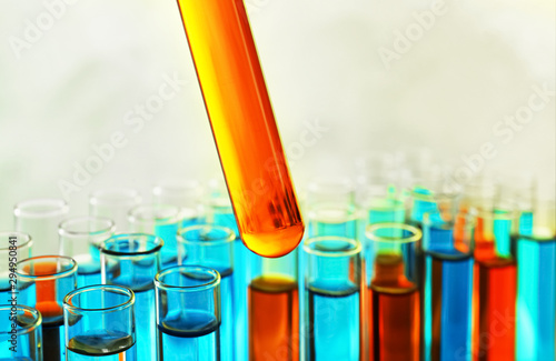 Foto Taking test tube with liquid sample on color background, closeup