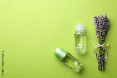 Female deodorants and lavender flowers on green background, flat lay Wallpaper Mural