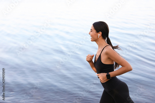 Photo Young sportswoman with wireless earphones running near river