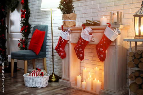 Photographie  Red Christmas stockings with gifts on decorative fireplace in festive room inter