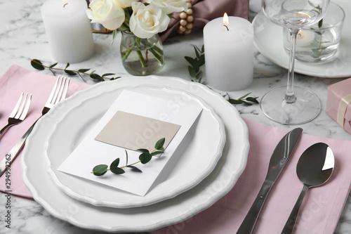 Fotografija Elegant festive table setting with blank card on white marble background
