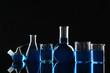 Leinwandbild Motiv Laboratory glassware with blue liquids on black background