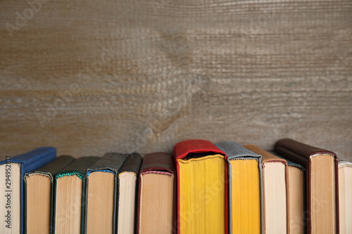 Stack of hardcover books on wooden background. Space for text Fototapet
