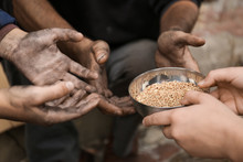 Woman Giving Poor Homeless People Bowl Of Wheat Outdoors, Closeup