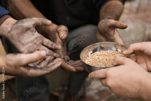 Fototapeta Woman giving poor homeless people bowl of wheat outdoors, closeup