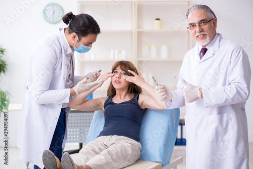 Deurstickers Wanddecoratie met eigen foto Two male doctors and young woman in plastic surgery concept