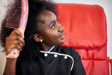 Young Woman Combing Her Hair In Front Of Red Chair
