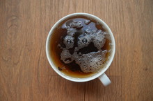 Bubbles In Cup Of Tea Look Like A Face. Illustration Of Visual Illusion - Pareidolia.  Fantastic Alien Or Goat With Big Eyes
