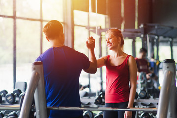 Fototapeta na wymiar Fitness woman and man with sportswear giving each other a high five while training on exercise at gym sport, bodybuilding, lifestyle and people concept