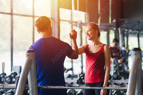 Fitness woman and man with sportswear giving each other a high five while training on exercise at gym sport, bodybuilding, lifestyle and people concept