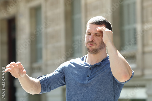Fototapeta Dizzy adult man suffering headache in the street