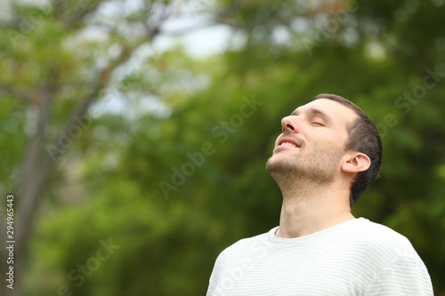 Fototapety, obrazy: Happy man breathing deeply fresh air in a forest