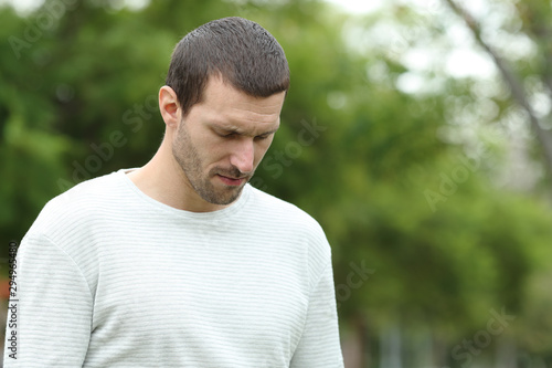 Obraz Sad man walking alone looking down in a park - fototapety do salonu
