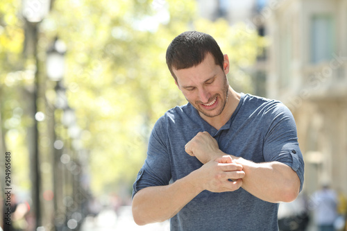 Fotomural Adult man scratching itchy arm in the street