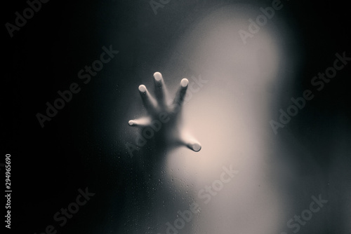 Foto Black color version of Creepy man holding the frosted glass with one hand