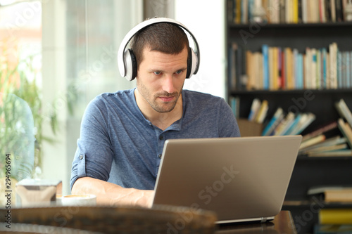 Fototapety, obrazy: Adult man wearing headphones using a laptop