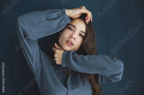 Beauty young girl in a dark blue shirt keeps her hands near her face against a d Tableau sur Toile