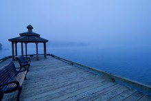 Bench And Boardwalk On A Misty Lake